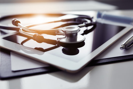Healthcare and technology concept - tablet and stethoscope on white table