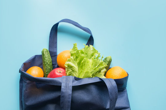 Zero waste concept. Blue shopping textile bag with fresh orange and vegetables. Space for text.