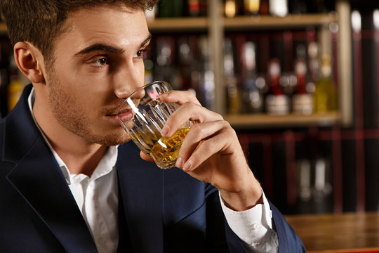The night is young. Closeup shot of a handsome man looking away thoughtfully drinking whiskey at the bar