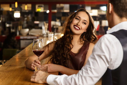 Smile speaks more than words. Beautiful young woman holding a glass of wine smiling joyfully to her man on a date at the bar