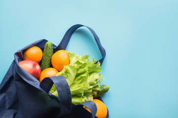 Zero waste concept. Blue shopping cotton textile bag with fresh orange and vegetables. Space for text.