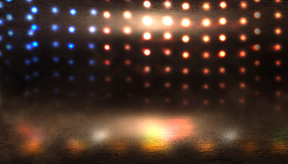 Dark empty stage, multicolored rays of neon searchlight, wet asphalt, smoke, night shooting, bokeh color.