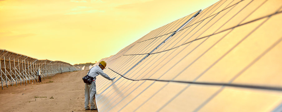 Asian engineer patrolling the desert solar photovoltaic power station in the sunset