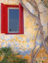 Athens Greece, red window of picturesque house exterior, Anafiotika district in Plaka old neighborhood