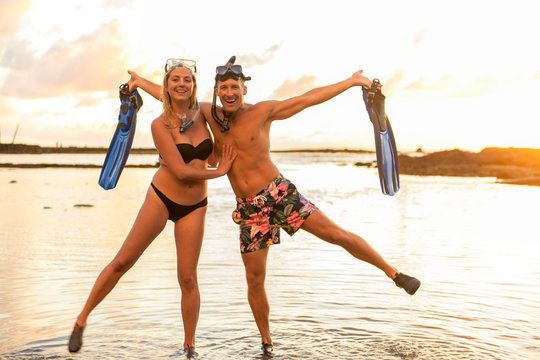 Couple is going to swim and snorkle on hawaii beach at the sunset