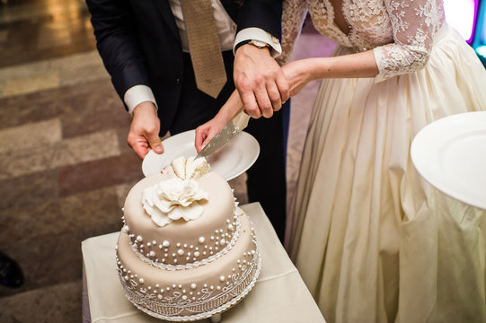 The bride and groom cut the wedding cake at a Banquet in a restaurant