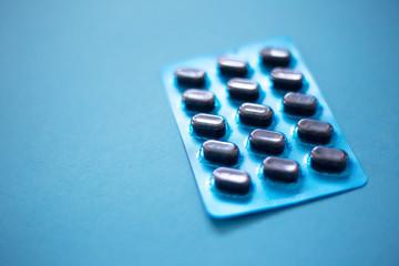 Dark blue medicine pills on the blue background.