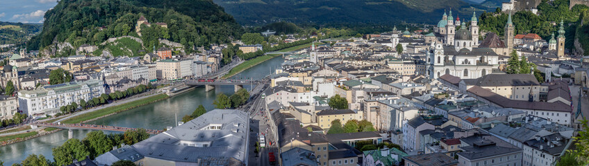 Panoramic view of the Salzburg Cityscape, with the Salzach river on the left and the Salzburg Cathedral on the right side. Photo was taken in summer
