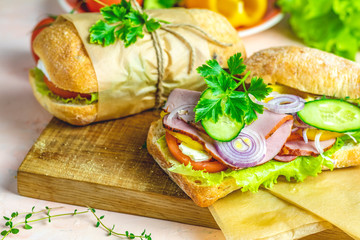 Sandwich with ham, tomato, cheese, pepper, onion and salad