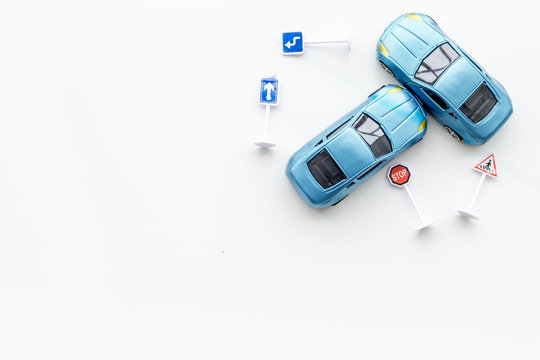 Car insurance concept with car toys on white background top view copyspace