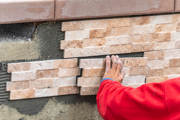 Worker Installing Wall Tile at Construction Site