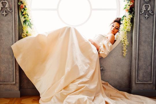 Tender charming princess in white satin dress