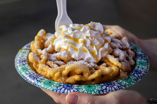 Funnel Cake Covered in Whipped Cream, Caramel Sauce, and Powdered Sugar Held in Hands at the San Diego County Fair, California, USA