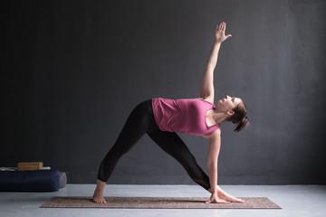 Girl standing in Utthita Trikonasana, extended triangle pose.