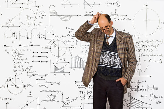 Middle aged caucasian mathematician explaining equations on a white wall