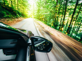 new modern car driving fast into forest with tall trees and empty mountain highway escaping running evading from all concept concept