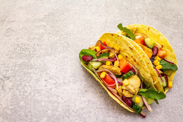 Mexican taco with chicken meat, red beans, fresh vegetables. Latin american food, stone background, copy space.