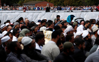 A woman takes photo with her mobile phone of people attend the Friday prayers at Hagley Park outside Al-Noor mosque in Christchurch