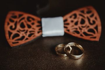 a705bf9ccad Two golden wedding rings on brown leather sofa. Grooms wooden bow tie in  the background