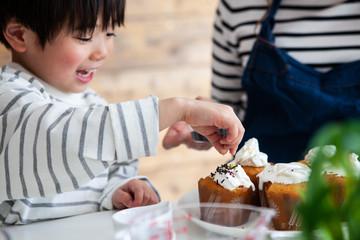 ケーキにチョコのトッピングをする男の子