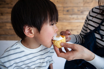 母親にカップケーキを食べさせてもらう子供