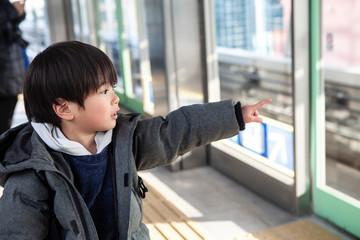 駅のホームから外を指差す男の子