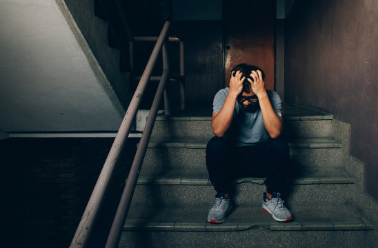 Depressed man sitting on the stairs in building and holding his forehead while having headache.Depression concept