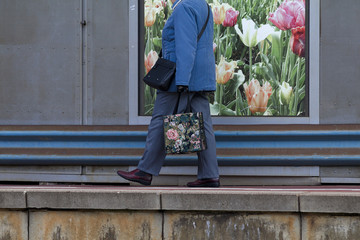 Walking old woman with bag with flowers on it in front of a poster with tulips on the platform of a railway station