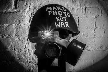 Art picture of military gas mask and green helmet on white brick wall with shadows, the inscription make photo not war on Fatherland defender day. Сoncept of calling world peace without hatred and war