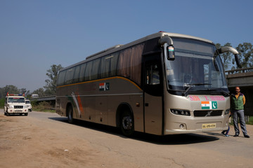 Passengers disembark the India-Pakistan 'friendship bus' under police guard at a rest stop in Sirhind
