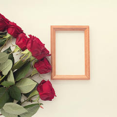 red roses on a light square background and a frame for a photo