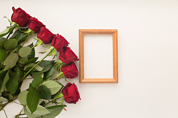red roses on a light background and a frame for a photo
