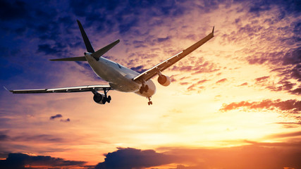 Airplane in the sunset sky flight travel transport airline background concept. Wall mural