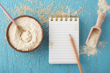 Quinoa flour in bowl with notepad and pencil
