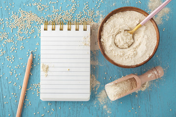 Quinoa flour in bowl with notepad on blue wooden table