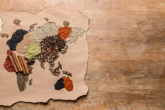 World map made of different spices on wooden background