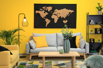Stylish interior of room with picture of map on wall