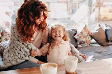 Inside portrait of young mother with little  daughter enjoying of good sunny day in cafeteria and drinking a cacao