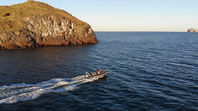 Speedboat passing island in Scotland with Bass Rock
