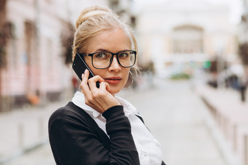Beautiful trendy blond business woman in glasses with smartphone and handbag of documents in her hands outdoors.