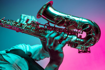 African American handsome jazz musician playing the saxophone in the studio on a neon background. Music concept. Young joyful attractive guy improvising. Close-up retro portrait. Fotomurales