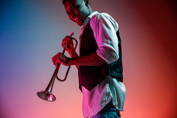 African American handsome jazz musician playing trumpet in the studio on a neon background. Music concept. Young joyful attractive guy improvising. Close-up retro portrait. Wall mural