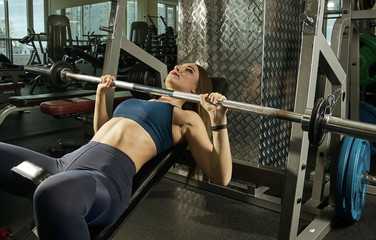 sporty woman builds muscle arms and chest on the simulator