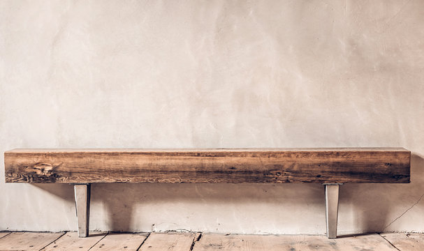 Rustic wooden bench near the plastered wall