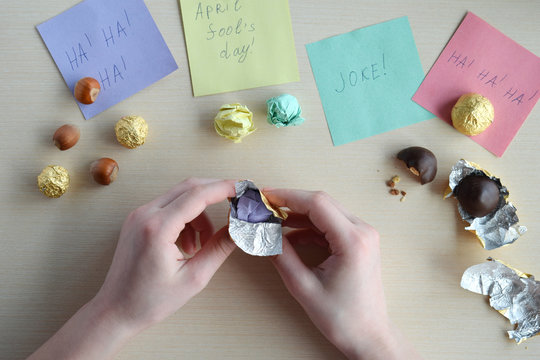April fools day prank. Wrapping hazelnut in candy wrappers on wooden table. Joke with food.