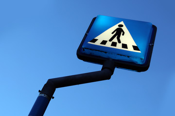 Traffic sign for pedestrian crossing. Real, blue sky.