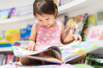 Little girl reading a book. Education. Wall mural