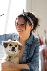 Beautiful female artist painting with her dog