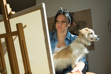 Beautiful artist painting with little dog in her lap