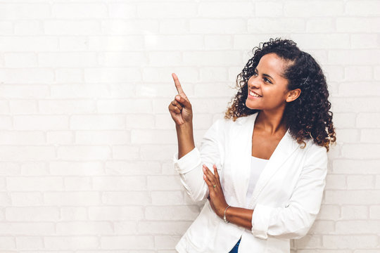 Smiling african american black woman pointing to empty copy space standing on white brick wall background